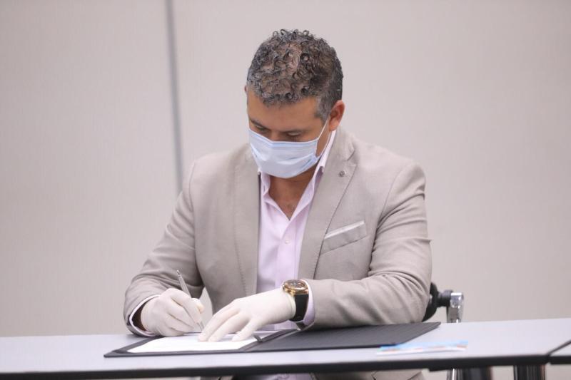 Helmut Cáceda firmando acuerdo